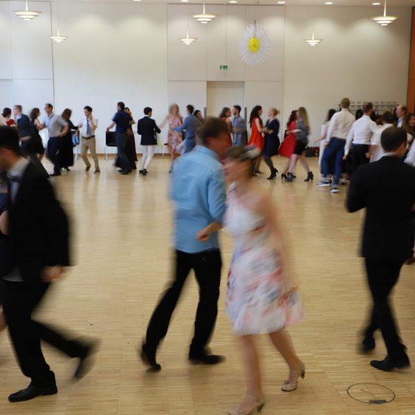 Der große Ballsaal ist gefüllt mit Menschen, die jeweils in Zweier-Pärchen eine Polka tanzen. Alle sind in einem riesigen Kreis aufgestellt.